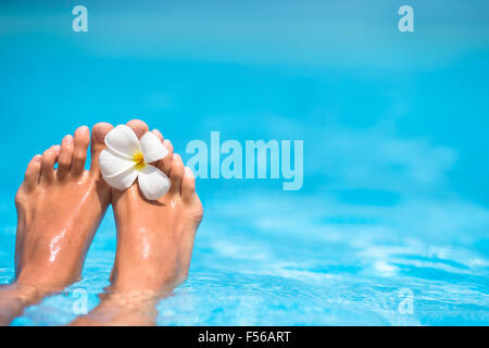 Frangipani flower between fingers on feet in outdoor swimming pool - Stock Photo