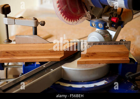 Sliding compound mitre circular saw cutting mitre in wood - Stock Photo