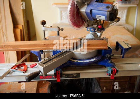 Sliding compound mitre circular saw on saw table cutting mitre in wood - Stock Photo
