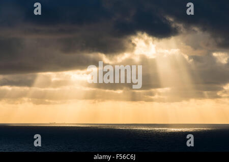 West Bay, Dorset, UK.  28th October 2015.  UK Weather - Beams of light shining through the clouds and onto the sea - Stock Photo