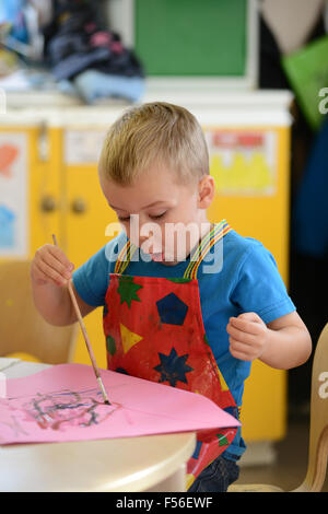 A little boy painting at nursery school. - Stock Photo