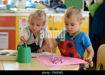A little girl & boy painting at nursery school. - Stock Photo