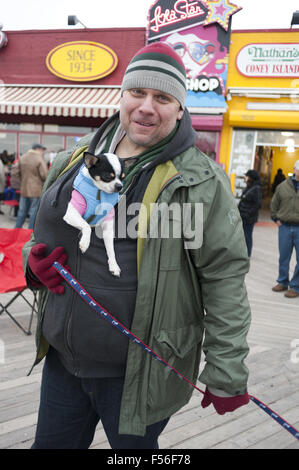 Man walks his dogs on winter day on Coney Island boardwalk in Brooklyn, New York, 2013. - Stock Photo