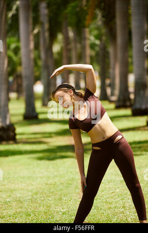 Young blond woman warming up before starting her daily sport routine. The girl does arms stretching in park, near - Stock Photo