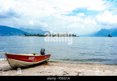A boat docks in front of Isola Pescatori on Lake Maggiore in summer. - Stock Photo