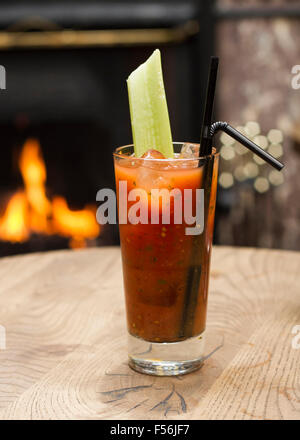 Bloody Mary Cocktail with a celery stick in front of a fire place - Stock Photo
