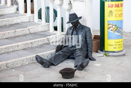 Street entertainer painted black posing as a drunk, sitting at the foot of steps, Venice, Italy, with hat for tips - Stock Photo