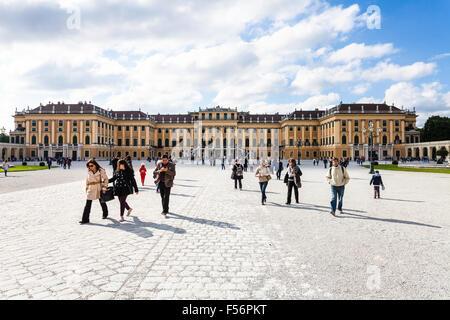 VIENNA, AUSTRIA - SEPTEMBER 29, 2015: tourists go from Schloss Schonbrunn palace to main entrance. Schonbrunn Palace - Stock Photo