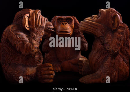 Three wise monkeys. Figurines of wood on a black background. - Stock Photo