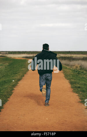 Middle aged man running in rural coastal area - Stock Photo