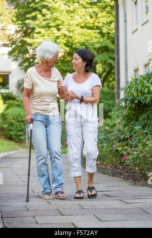 Elderly care at home, Nurse cares for an elderly woman, walking with walking aids, - Stock Photo
