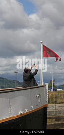 Tourist on the SS Nomadic taking a photograph of The White Star Line pennant. Nomadic is berthed in Belfast's Titanic - Stock Photo