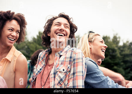 A young couple, a man and woman among others outdoors in the countryside. - Stock Photo