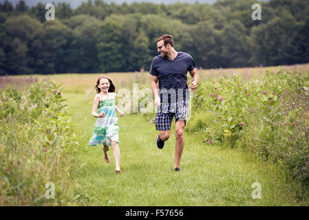 A man and a young child running through a wildflower meadow. - Stock Photo