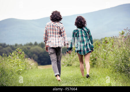A couple, man and woman walking through a meadow hand in hand, rear view. - Stock Photo