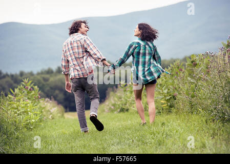 A couple, man and woman running through a meadow hand in hand. - Stock Photo