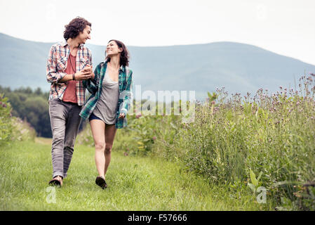 A couple, man and woman walking through a meadow in the countryside. - Stock Photo