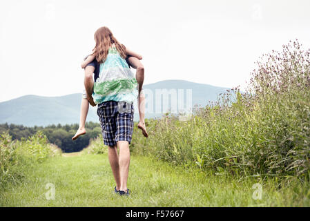 A man giving a young child a piggyback in a meadow. - Stock Photo