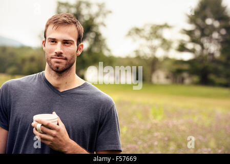 A young man holding a coffee cup standing in a field by a lake. - Stock Photo