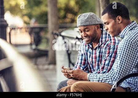 Two men sitting in a park, looking at a smart phone - Stock Photo