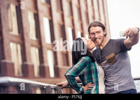 A woman kissing a man on the cheek, posing for a selfie by a large city building - Stock Photo