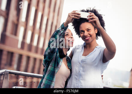 Two women posing and taking a selfie by a large building in the city - Stock Photo