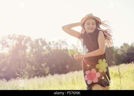 A child, a young girl in straw hat in a meadow of wild flowers in summer. - Stock Photo