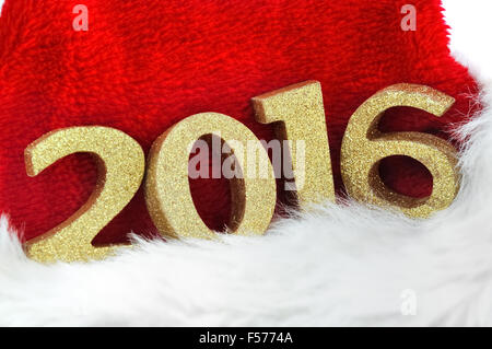 close on golden figures 2016 on a santa claus hat on white background - Stock Photo