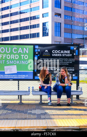 Two young women sit on a Metro platform seat waiting for the next tram in Minneapolis - Stock Photo