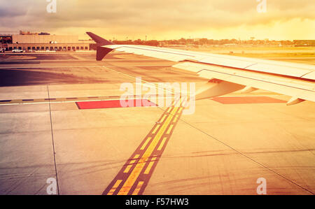 Vintage toned plane wing above runway at sunset, travel concept. - Stock Photo