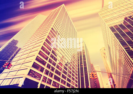 Vintage toned skyscrapers with motion blurred sky, modern business background.
