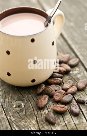 the cocoa drink and cocoa beans on old wooden table - Stock Photo