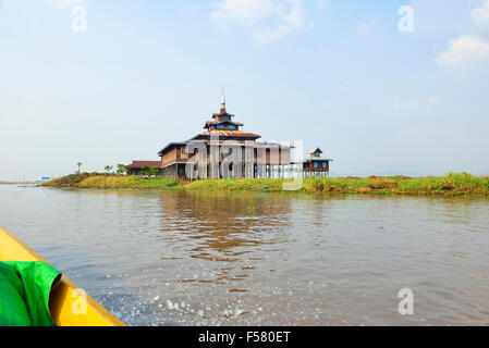Tourists traveling in a long-tailed motorised boat (bottom left )passing a temple on an island on a tributary to - Stock Photo