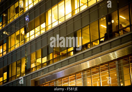 Modern office building with windows lit up at night - Stock Photo