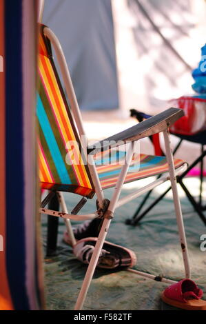 Sun lounger with orange , blue, red and yellow stripes in a camping scene - Stock Photo