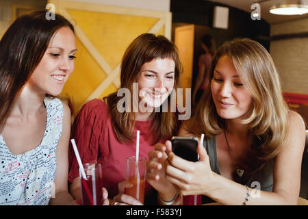 friends talking in cafe and looking at the photos on smart phone - Stock Photo