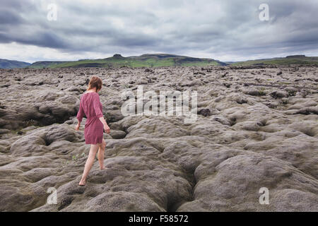 fashion woman walking barefoot in lava field in Iceland - Stock Photo