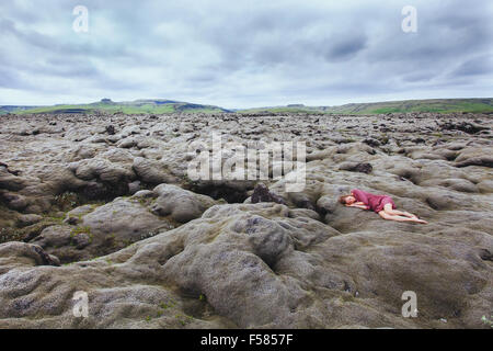 beautiful girl in red dress sleeping in lava field in Iceland, solitude concept - Stock Photo