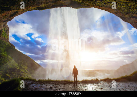 incredible waterfall in Iceland, silhouette of man enjoying amazing view of nature - Stock Photo