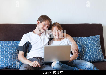 happy smiling couple with laptop at home, shopping online - Stock Photo