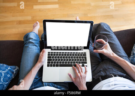 couple using computer with empty screen, banking or shopping online - Stock Photo