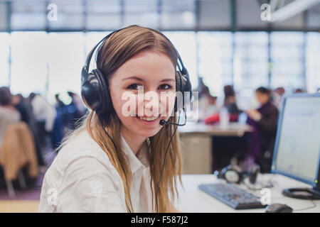 happy student with headphones and computer in university - Stock Photo
