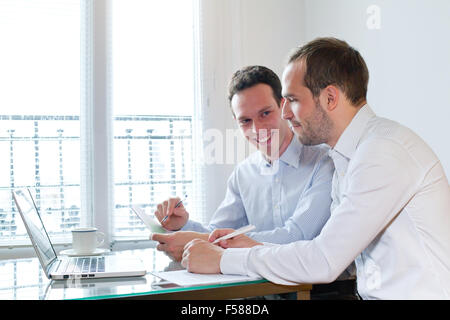 two smiling happy business men working on project in the office - Stock Photo