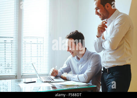 two young business men laughing in front of computer - Stock Photo