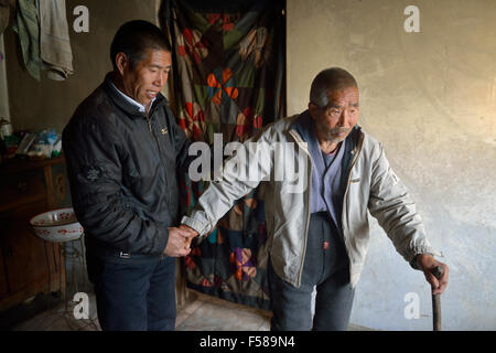 Wu Deyi, 48, who never merried because of poverty, support his father Wu Hai, 83, who suffers with brain atrophy - Stock Photo