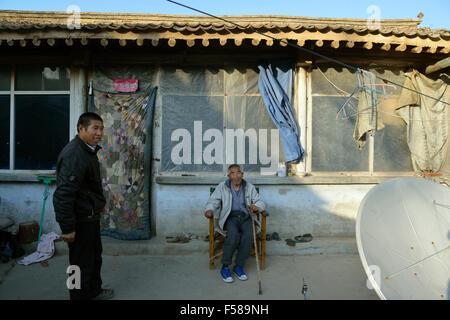 Wu Deyi, 48, who never merried because of poverty, takes care of his father Wu Hai, 83, who suffers with brain atrophy - Stock Photo