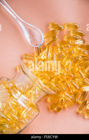 fish oil capsules splash from glass bottle and spoon beside - Stock Photo