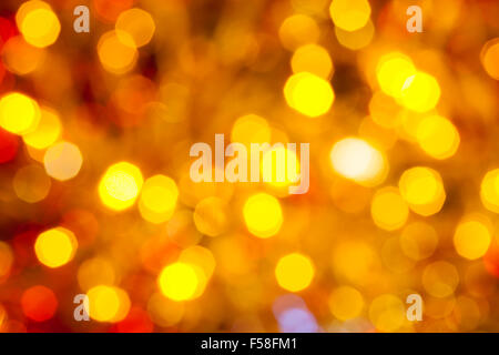 abstract blurred background - brown, yellow and red flickering Christmas lights bokeh of electric garlands on Xmas - Stock Photo