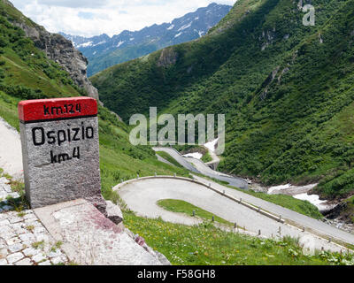 Milestone and serpentines of  the historic cobble stone paved Gotthard mountain pass road (Tremola) in the Swiss - Stock Photo