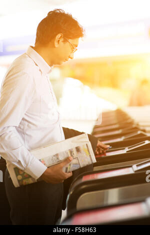 Asian Indian businessman at entrance of railway station, touching ticket token on gate barrier during sunset, beautiful - Stock Photo